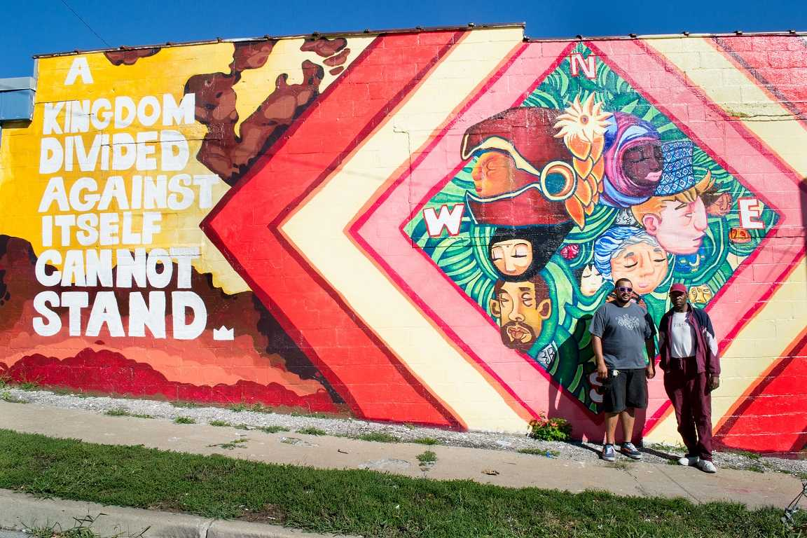 Daniels poses with a neighborhood beneficiary of his latest mural off Independence and Norton