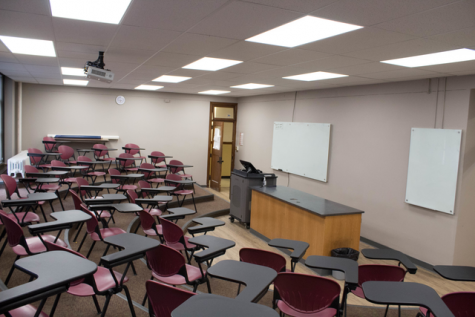 Science Hall room 310 with a view from the student's perspective in the back corner. White boards and the professor's podium can be seen.