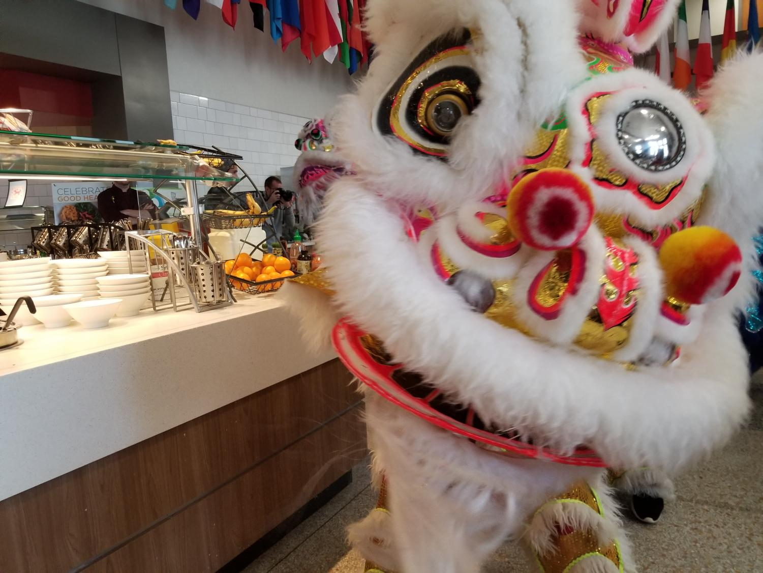 Pho Hien Troop's yellow lion dancing in the cafeteria at Park University