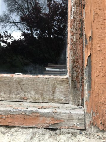 Window frame with rotted wood and chipped paint