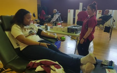 Biology senior Brooklyn Campbell laying on a hospital bed giving blood for the american red cross