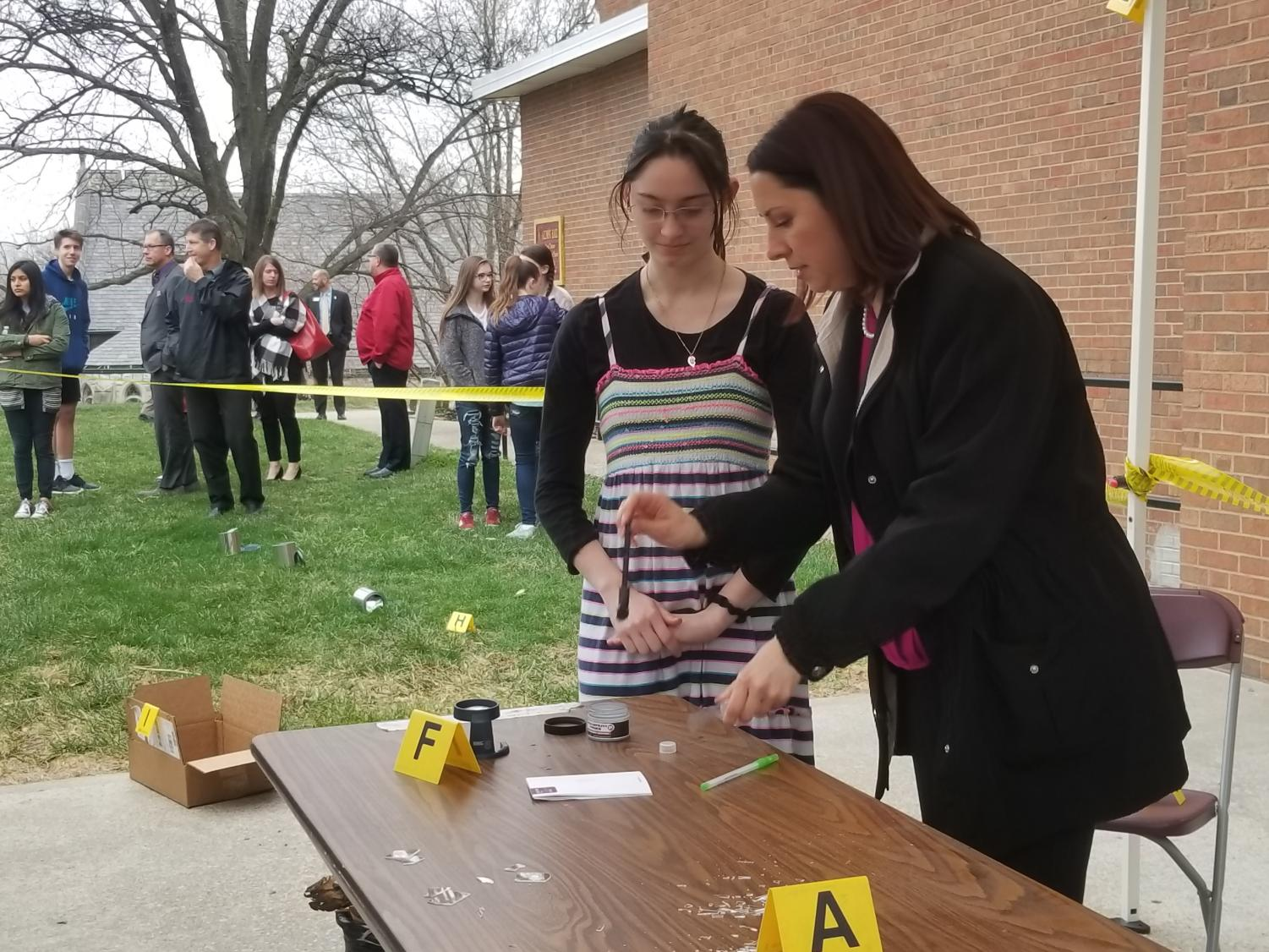 Tatiana Trejos demonstrating how to dust for fingerprints at a crime scene