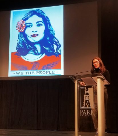 Paola Mendoza standing on stage with a poster of a woman with a flower in her hair speaking about the influence art had on the Women