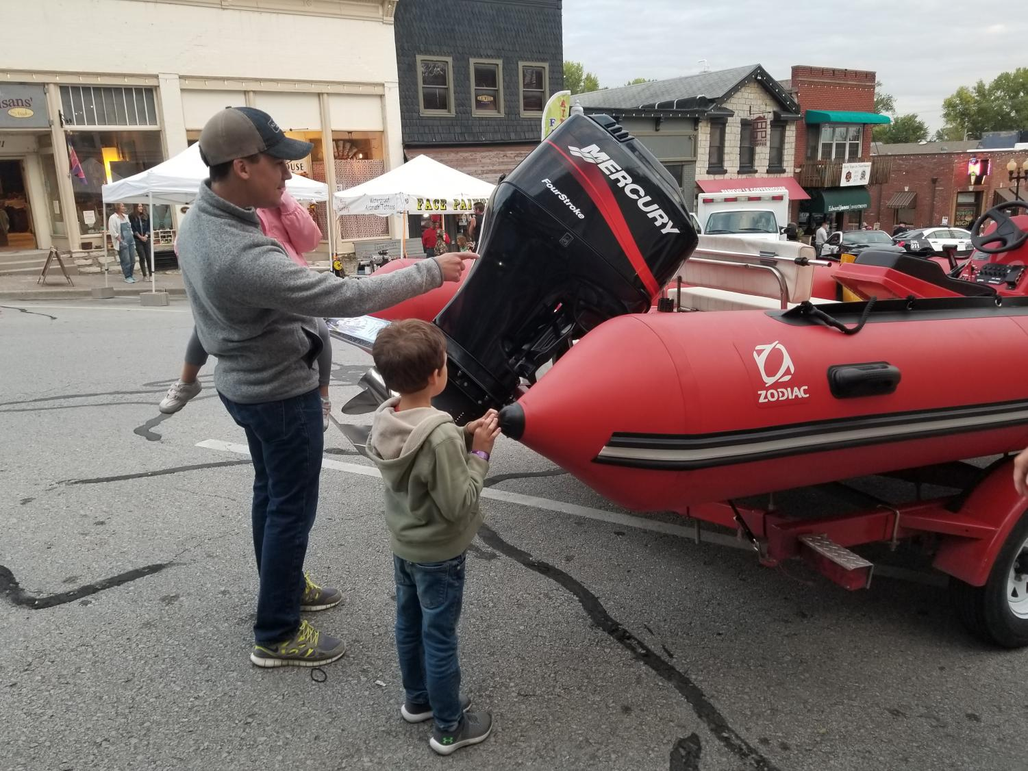 Lucas Ramon, age 7, asks his father questions about the Parkville search and rescue boat.