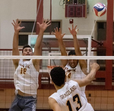 Felipe Chagas and Caio Alves jump with their arms reached upwards to try to block the volleyball that is being spiked towards them by a Graceland University player.
