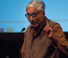 Rajmohan Gandhi speaking on stage. He holds up his pointer finger to emphasize his point.