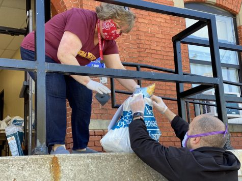 Laurie Gunderson, Park University's first lady, passes a bag of pantry goods to Dean of Students, Jayme Uden, Ed.D., during a Friday evening pickup for Pirate Pantry.