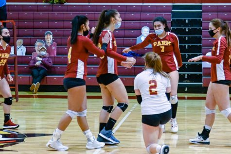 Volleyball players walk towards each other.