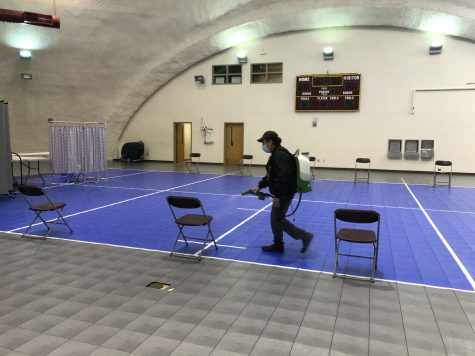 Campus workers disinfect seats before Covid testing begins.