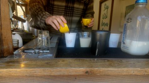 worker pours espresso into coffee